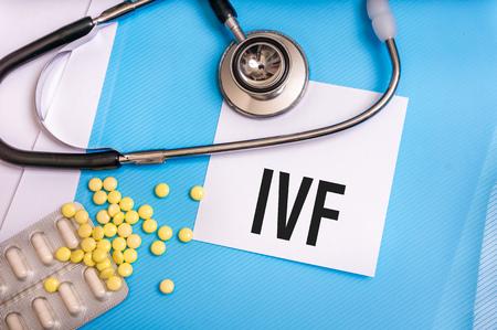 in vitro: Palabra de FIV escrita en la carpeta médica azul con archivos de pacientes, píldoras y un estetoscopio en el fondo