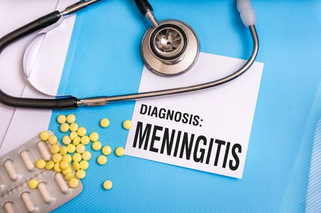 Meningitis word written on medical blue folder with patient files, pills and stethoscope on background