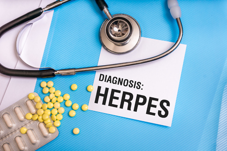 Herpes word written on medical blue folder with patient files, pills and stethoscope on background