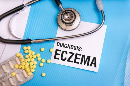 Eczema word written on medical blue folder with patient files, pills and stethoscope on background Stock Photo