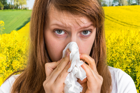 Woman with allergy on yellow rape field sneezing in tissue - blooming rapeseed field and allergy Stockfoto