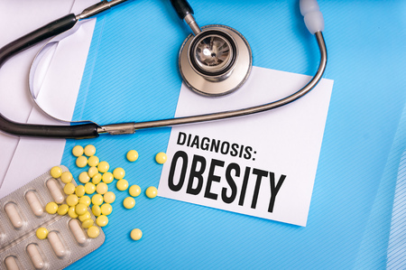 Obesity word written on medical blue folder with patient files, pills and stethoscope on background