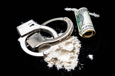 Handcuffs, money and cocaine drugs on black background Stock Photo