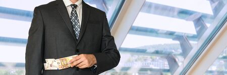 louver: Man in business suit with money in pockets in office Stock Photo