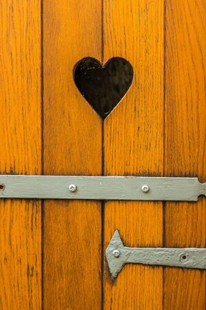 Old wooden door with heart decoration in Lindau. Stock Photo