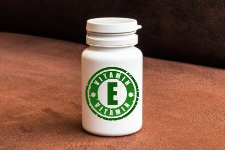 Bottle of pills with vitamin E on brown background. Stock Photo