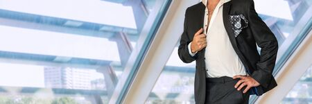 Disheveled man in black suit in office. Stock Photo