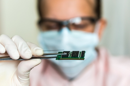 Young scientist holding and examining damaged electrical component Stock Photo