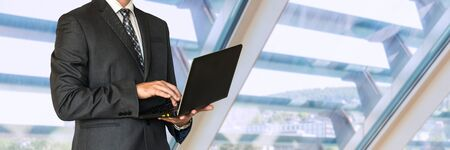 Businessman in black suit holding laptop in office