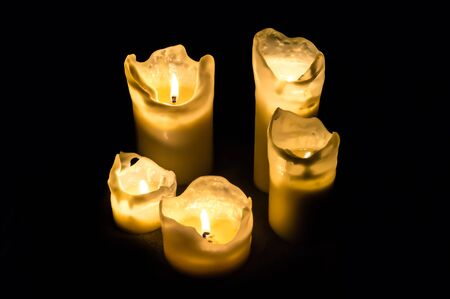 Five candles at night isolated in the dark background. Stock Photo