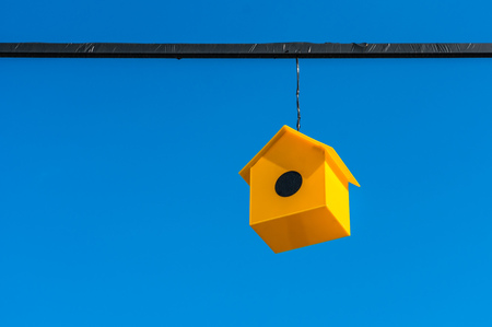 nesting: Nesting box or birdhouse for birds isolated on blue sky background