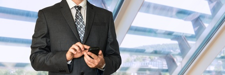 jalousie: Man in black suit holding mobile phone in office Stock Photo