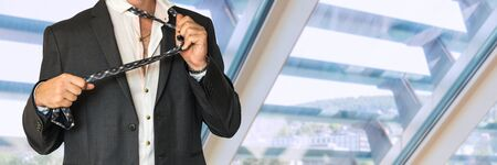 Disheveled man in a suit holding tie in office Stock Photo