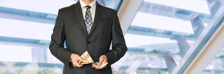 Businessman in black suit counting money in office Stock Photo