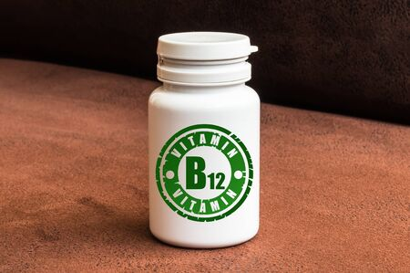 Bottle of pills with vitamin B12 on brown background. Stock Photo