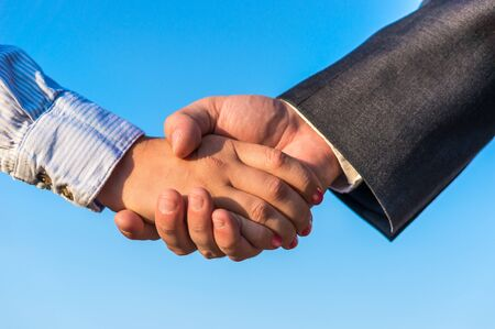 treaty: Business handshake on the blue sky background Stock Photo