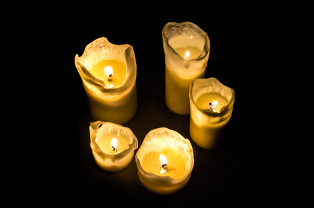Five candles at night isolated in the dark background
