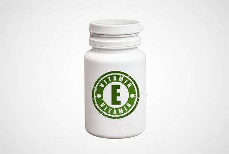 Bottle of pills with vitamin E on white background. Stock Photo