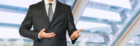 louver: Man in business suit gestures with hands and says something in office