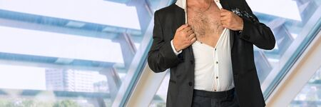 Disheveled man in business suit with an unbuttoned shirt in office