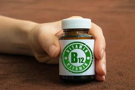 Human hand holding a bottle of pills with vitamin B12 on brown background Stockfoto