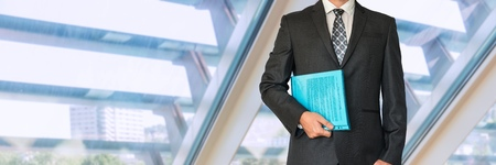 Businessman in suit holding documents in office