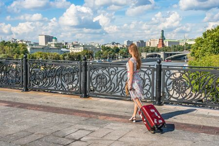Young traveler woman walking and carrying a suitcase in Moscow not far from Kremlin, Russia