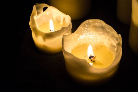 Two candle flames at night in the dark background