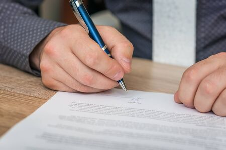 Businessman is signing a contract to conclude a deal - business concept. Stock Photo