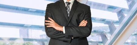 louver: Businessman in black suit with folded hands in office Stock Photo