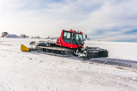Red snow-grooming machine on snow in Czech mountains Stock Photo