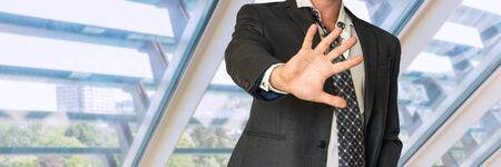 louver: Man in suit gestures leave me alone in office Stock Photo