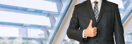 louver: Man in business suit showing symbol OK in office Stock Photo
