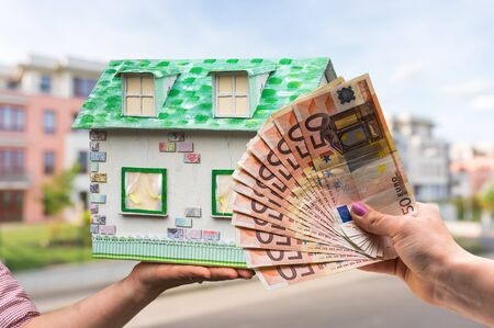 Real estate agent holding model house from paper and new property owner buying it by euro money on blurred background