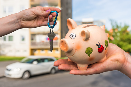 hypothec: All savings money from pink ceramic piggy bank to pay for the dream home on blurred background