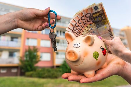 Real estate agent giving flat keys to a new property owner, who is paying by euro money banknotes from piggy bank on blurred background Stock Photo