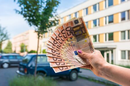 Property buyer holding euro banknotes and buying beautiful flat from real estate agencies on blurred background