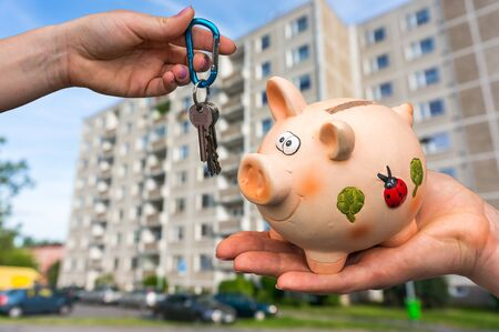 Real estate agent giving flat keys to a new property owner, who is paying last saving money from piggy bank on blurred background