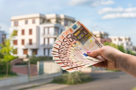 Property buyer holding euro banknotes and buying beautiful house from real estate agencies on blurred background