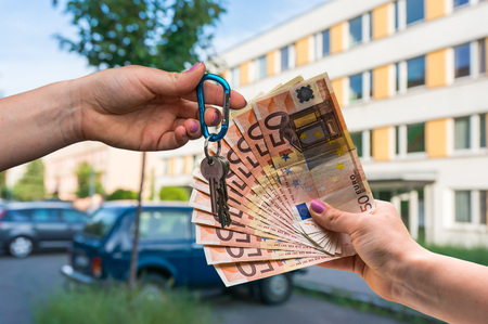 Real estate agent giving house keys to a new property owner, who is paying by euro money on blurred background