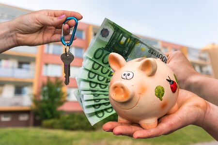 Real estate agent giving house keys to a new property owner, who is paying by euro money from piggy bank on blurred background. Stock Photo