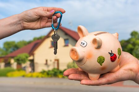 Real estate agent giving house keys to a new property owner, who is paying last saving money from piggy bank on blurred background
