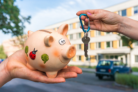 Real estate agent giving home keys to a new property owner, who is paying all saving money from piggy bank on blurred background Stock Photo