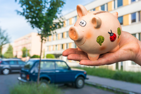 All savings money from pink ceramic piggy bank to pay for the dream home and car on blurred background Stock Photo