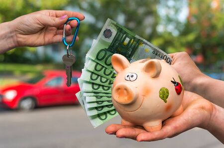 Salesman giving car key to a new car owner, who is paying last saving money from piggy bank on blurred background Stock Photo