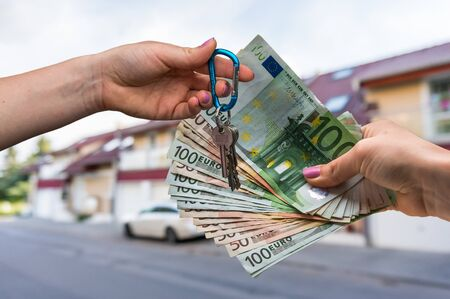 hypothec: Real estate agent giving house keys to a new property owner, who is paying by euro money on blurred background