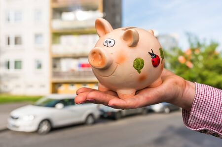 All savings money from pink ceramic piggy bank to pay for the dream home on blurred background. Stock Photo