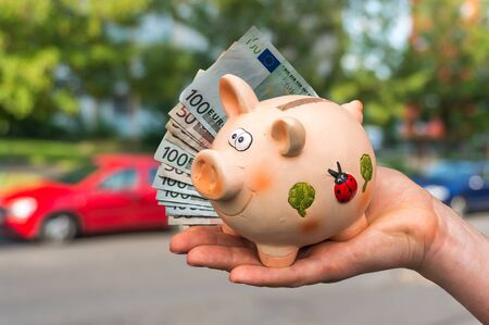 All savings money from pink ceramic piggy bank to pay for the dream car on blurred background