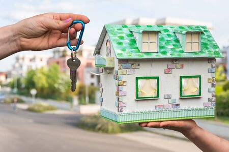 Real estate agent giving house keys to a new property owner, who is holding model house from paper on blurred background Stock Photo