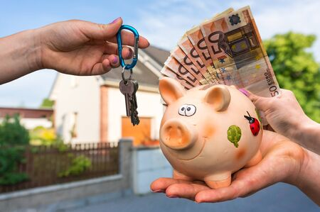 hypothec: Real estate agent giving house keys to a new property owner, who is paying by euro money from piggy bank on blurred background
